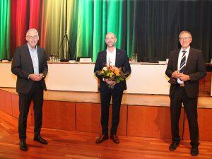 Landräte Helmut Riegger (li.) und Roland Bernhard (re.) gratulieren dem Geschäftsführer des Klinikverbundes Südwest Martin Loydl.